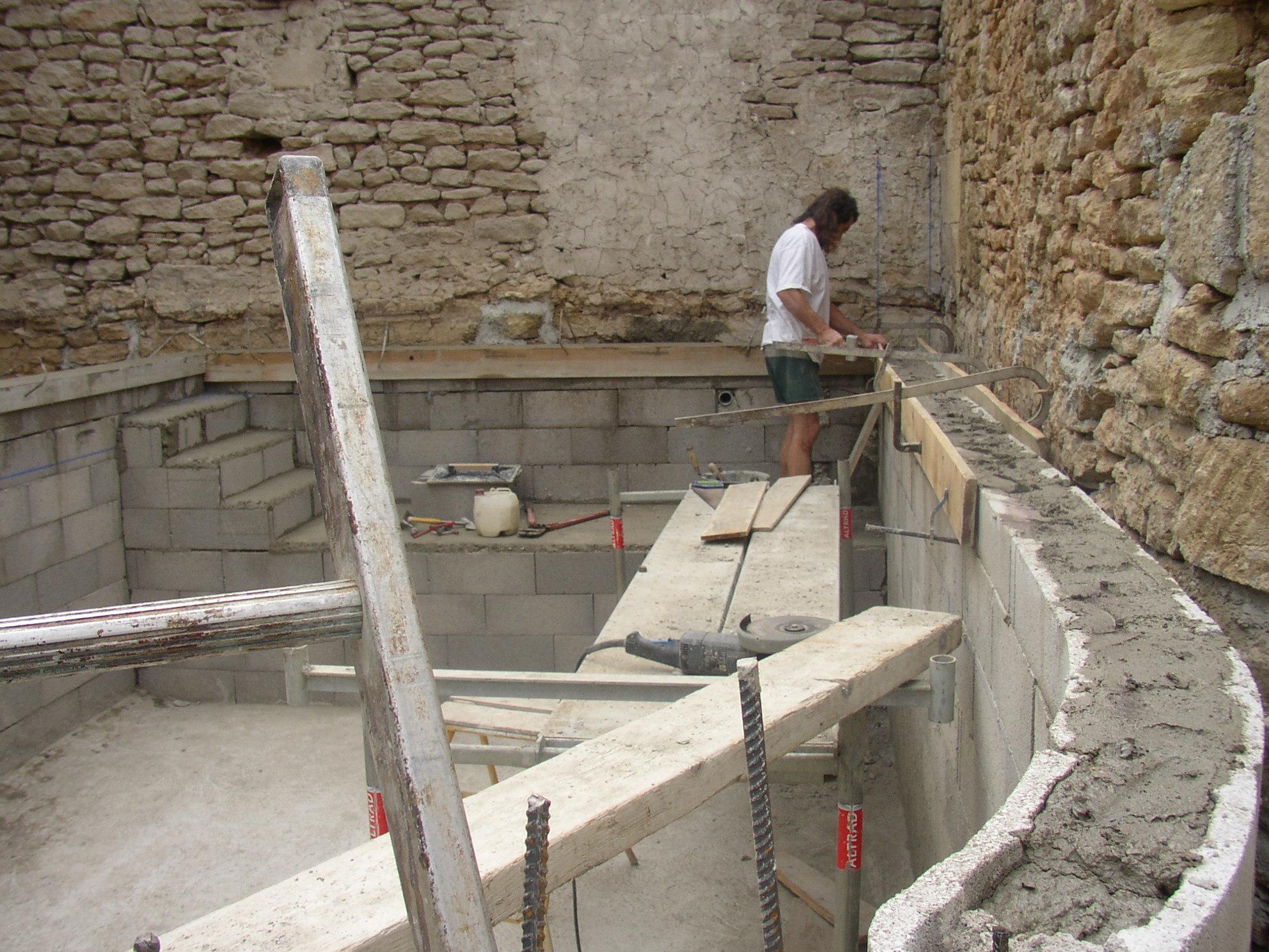 Desportes rénovation Gard. Murs en agglo à bancher, banquette et escalier béton dans la piscine.
