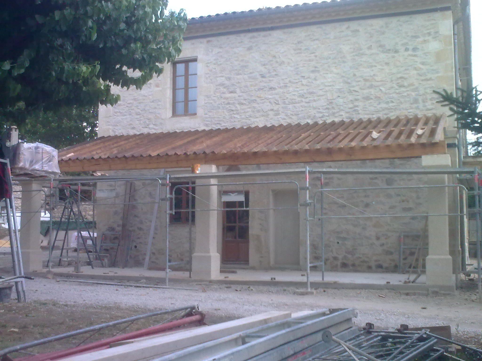 Restauration de la façade d'un mas dans l'Hérault, création d'un auvent, charpente traditionnelle piliers en pierres taillées.