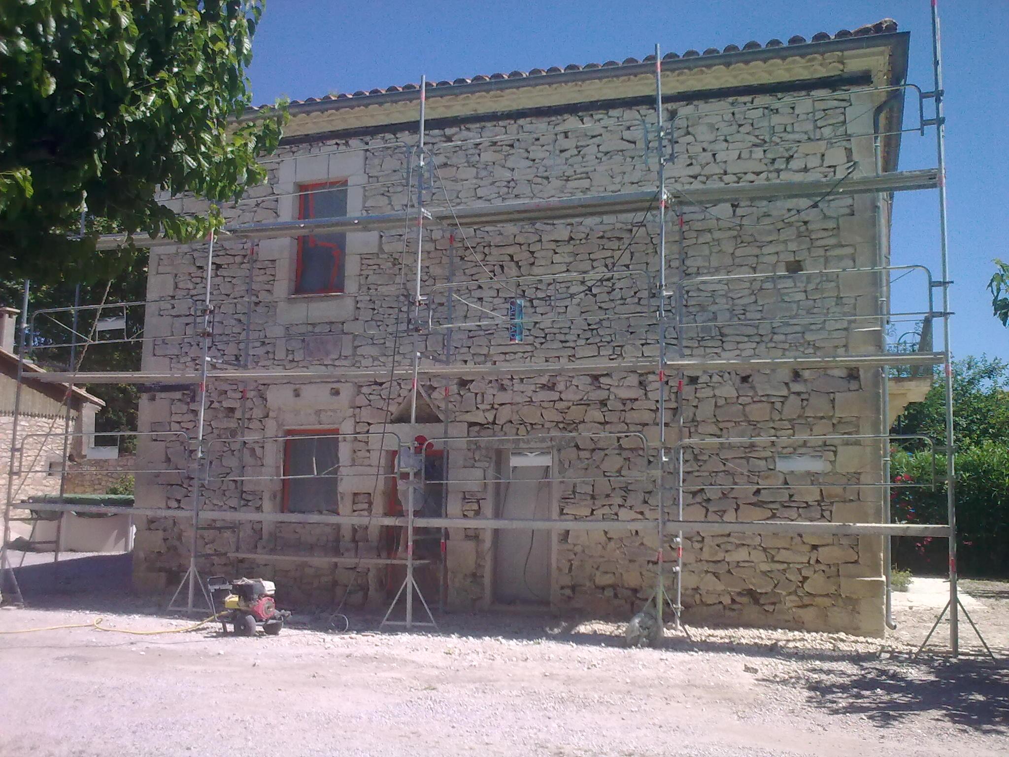 Restauration de la façade d'un mas dans l'Hérault, décroutage des pierres depuis échafaudage.