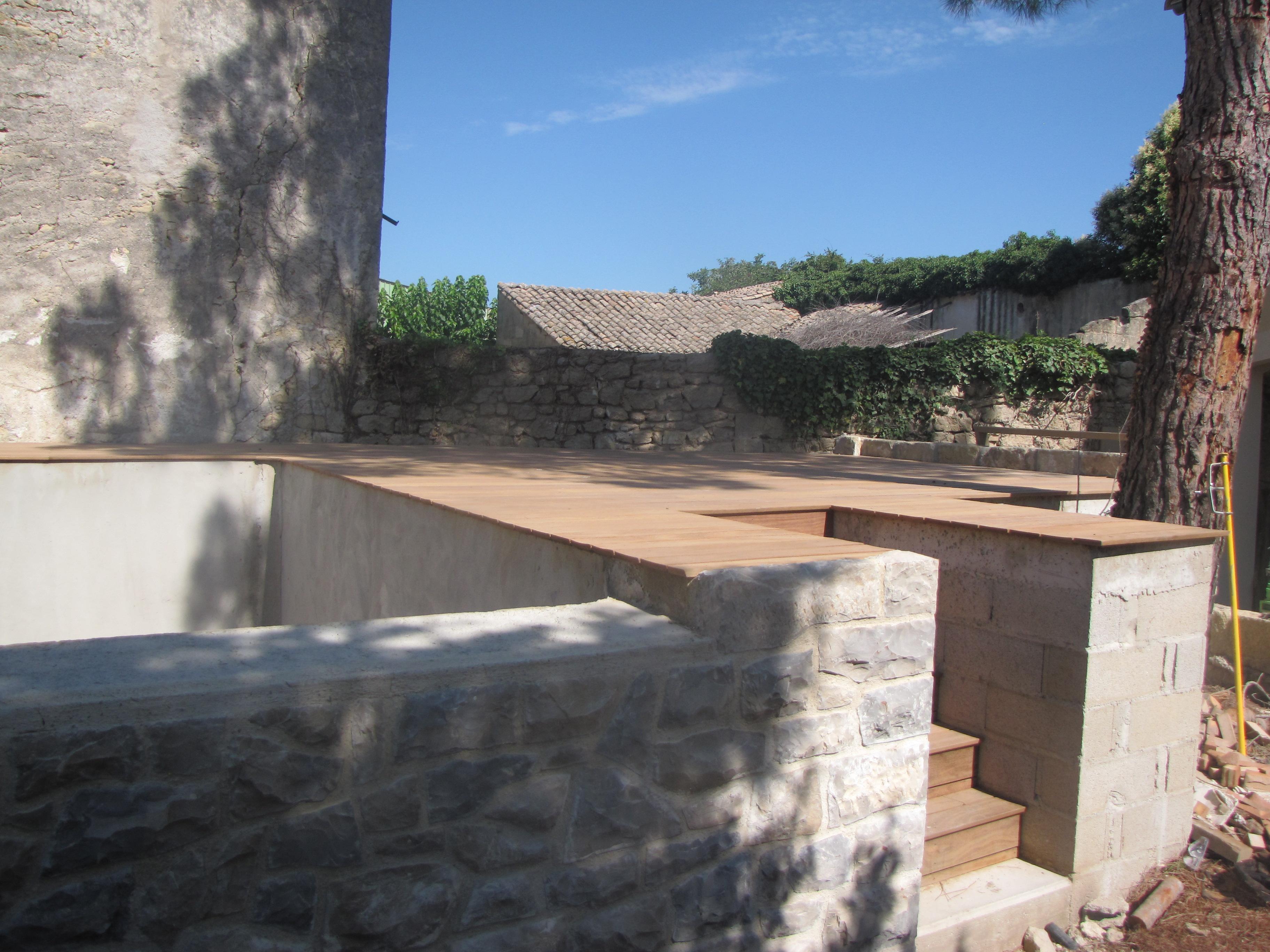 Desportes rénovation, Gard. Construction d'une piscine à débordement, habillage en pierre des extérieurs et plage en teck.