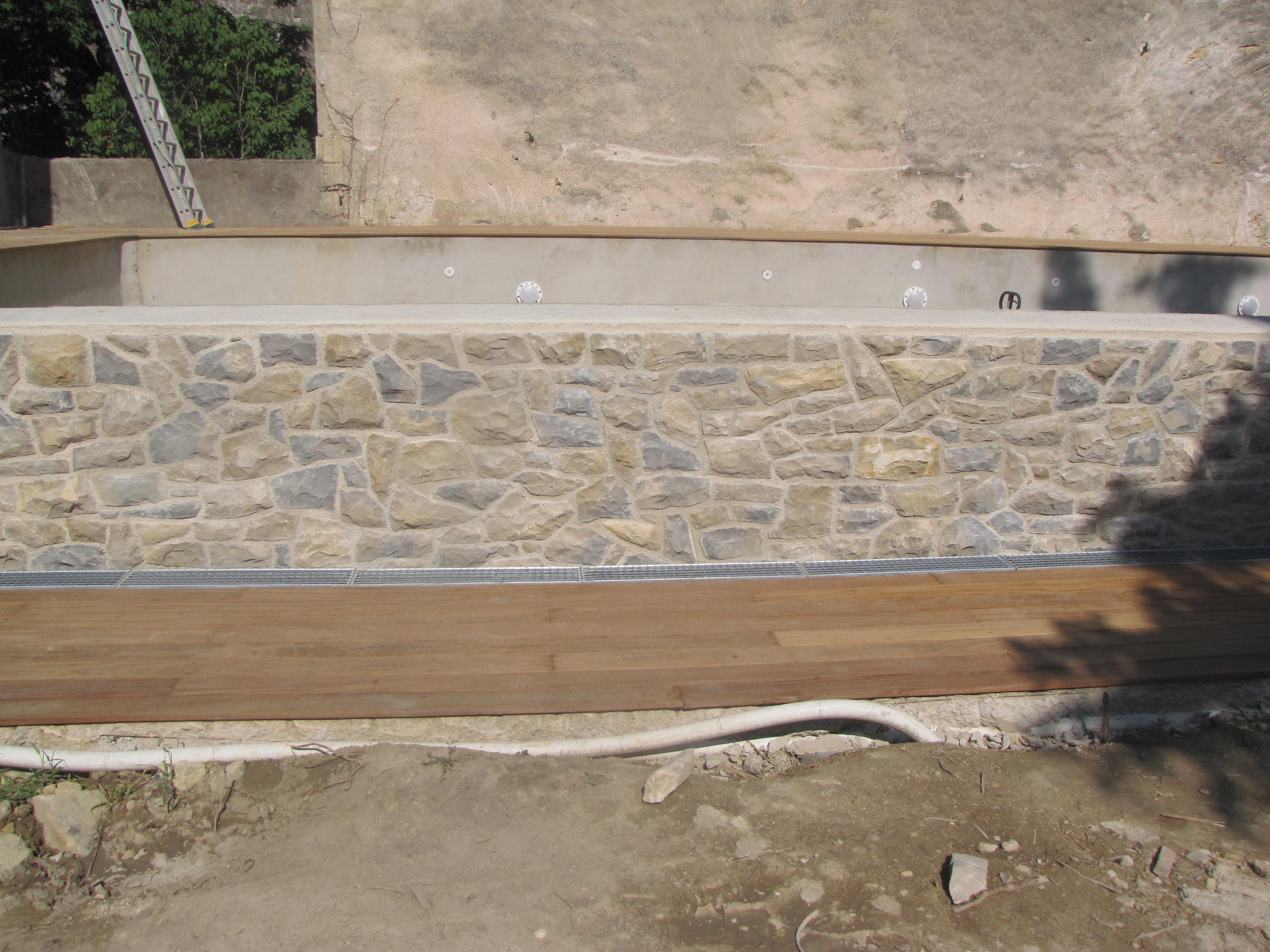 Desportes rénovation. Piscine à débordement Hérault. Habillage en pierres et en teck.